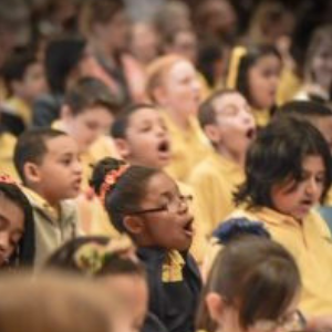 Students at Charter School for Applied Technologies sing along during the Link Up concert.